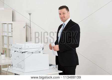 Happy Businessman Holding Paper By Photocopy Machine