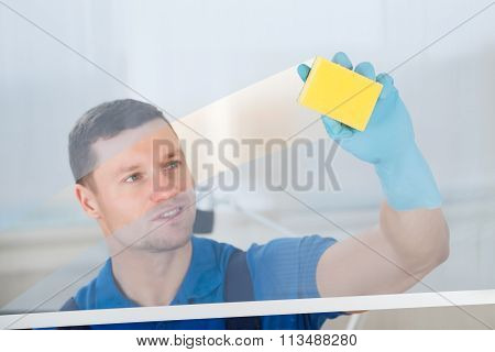 Mid adult male worker cleaning glass window with rag poster