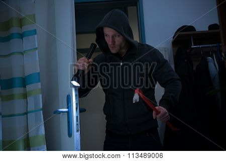 Robber With Crowbar And Flashlight Entering In House