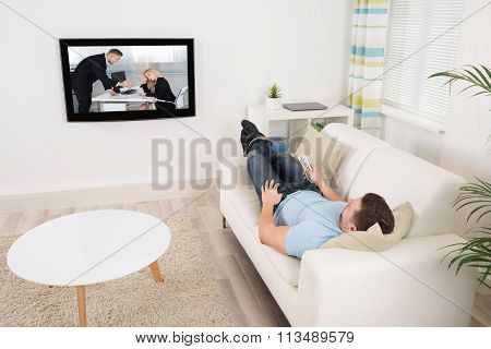 Relaxed Man Watching Movie In Living Room