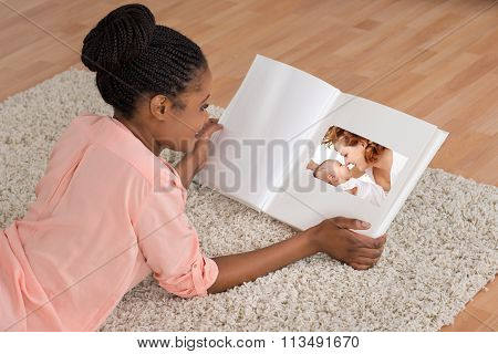 Woman Smiling While Looking At Photo Album