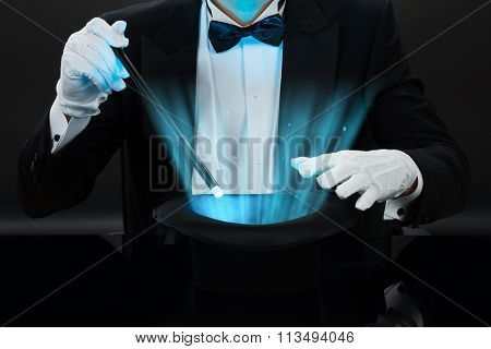 Midsection of magician holding magic wand over illuminated hat against black background poster