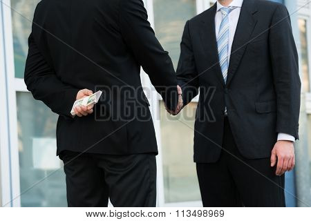 Businessman Holding Dollars While Shaking Hands With Partner