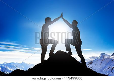 Male Friends Giving High Five On Mountain Peak