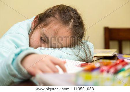 Young Girl Falling Asleep Doing Homework