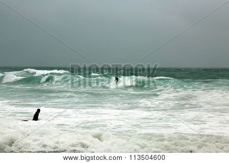 Laguna Beach CA: 1-6-2016, Surfers swim out to Surf the Higher than usual waves in Laguna Beach as the El Nino Storm of 2016 makes landfall and causes flooding and damage around southern California.