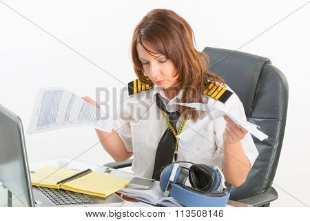 Overworked woman pilot wearing uniform with epaulettes holding papers in briefing room