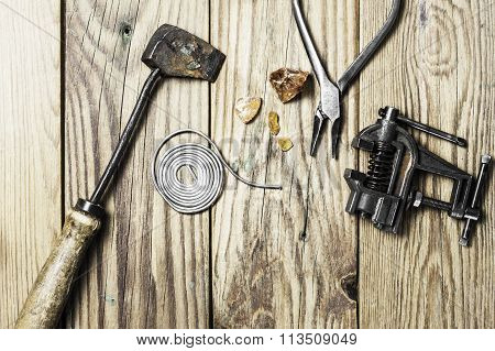 A vintage brazing copper  iron, a solid tin wire, some colophony, a grip vice and pliers on a wooden background poster