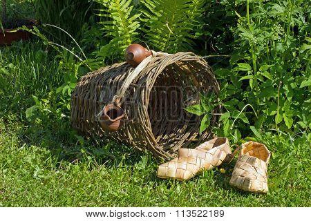 two woven birch bark handmade sneaker lying on the green grass