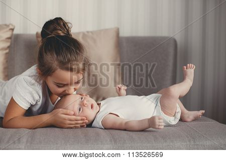 Little girl with a newborn baby brother