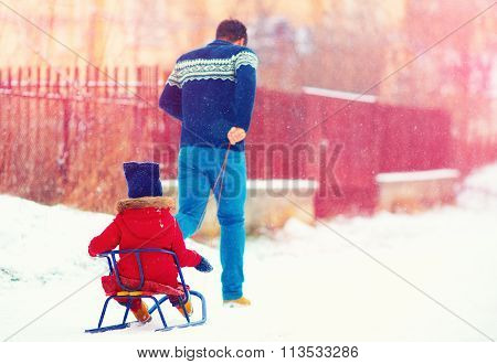 Happy Father And Kid Having Fun With Sledge Under Winter Snow