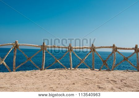 Wooden woven makeshift fence against the sea