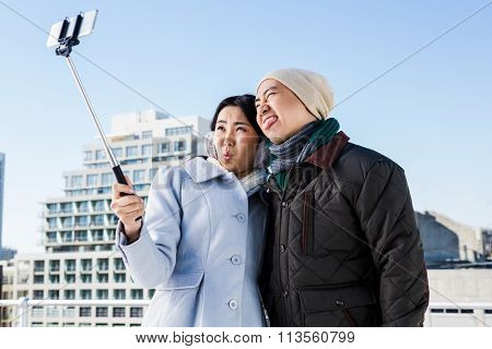 Couple making funny face while taking photo through selfie stick against building