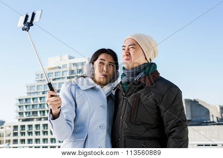Couple making funny face while taking photo in smart phone with selfie stick against buildings