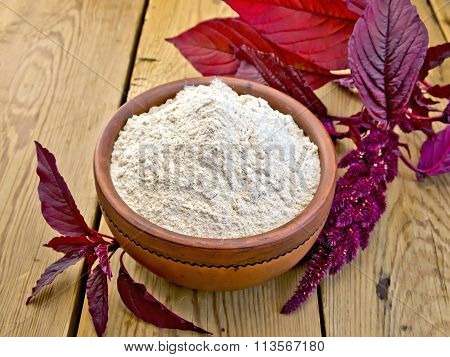 Flour amaranth in clay bowl on board with flower
