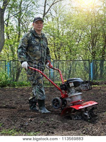 Man working in the garden preparing ground cultivator