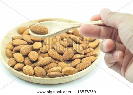 Hand On Spoon Of Almond Isolated On White Background