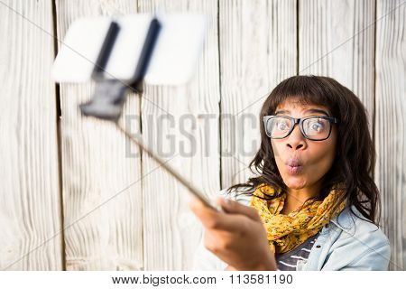 Casual smiling woman taking a selfie against wooden plank