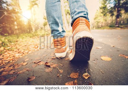 Woman Feet sneakers walking on fall leaves Outdoor