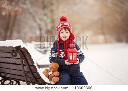 Cute Little Caucasian Boy With Teddy Bear And Red Lantern, Playing In The Winter Park