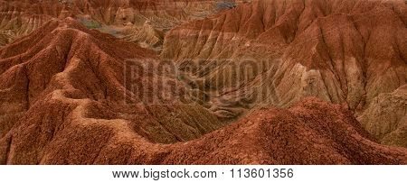 Cliff with cactus and valley of red orange sand stone rock formation in hot desert Tatacoa, Huila