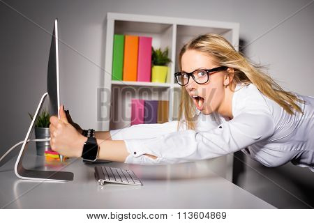 Woman in office holding on to computer