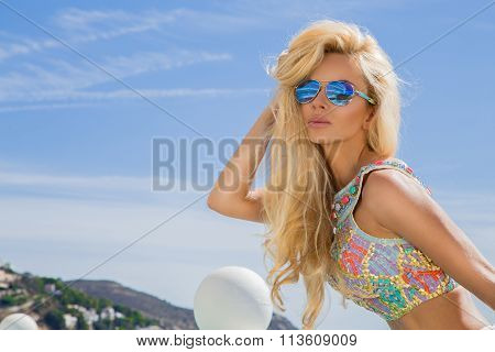 Beautiful blond hair sexy woman young girl model in sunglasses and elegant color swimsuit with crystals around the pool with a balustrade overlooking the sea and the island of Santorini