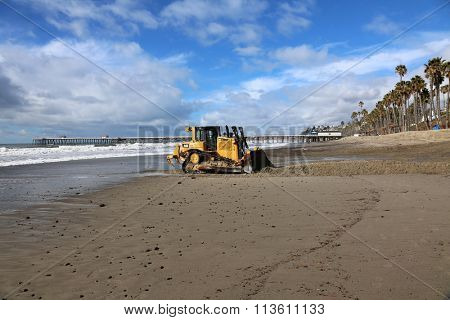San Clemente CA Jan. 7 2016: A bulldozer pushes sand back against a retaining wall in an attempt to repair damage caused by the El Nino of 2016 which caused extensive damage around southern california