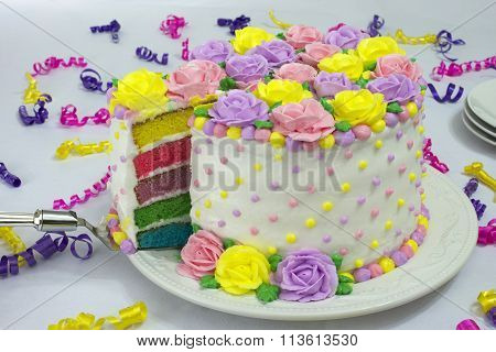 Single slice of pastel rose dot cake being pulled from cake showing colorful layers