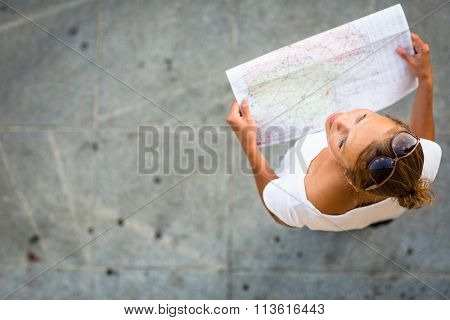 Pretty young female tourist studying a map, enjoying discovering a new city, looking excited (shallow DOF; color toned image)