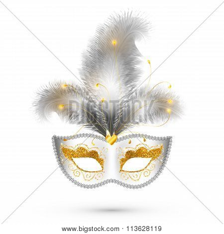 White carnival mask with golden glitter decoration and realistic silver feathers