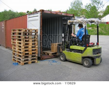 Man Picking Up Pallet With A Truck