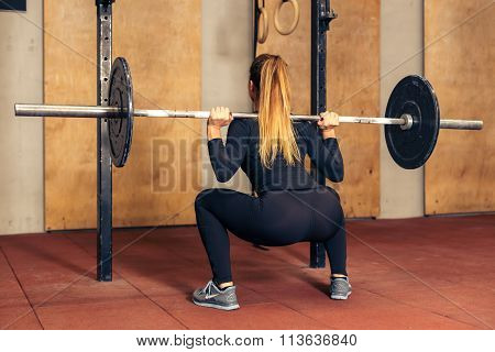 Back view girl doing heavy squat with barbell