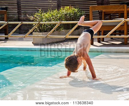 The boy somersaults in the water near the swimming pool
