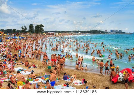 Crowded Beach And People In The Waves