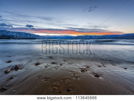 scenic shoreline view of mountain lake in winter at sunset