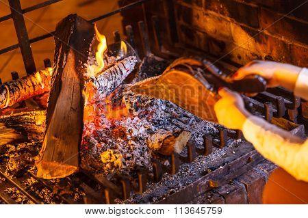 Closeup Hands Fireplace Making Fire With Bellows.