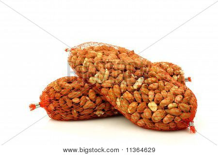 Bird feed in red plastic nets on a white background poster