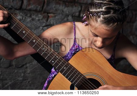 Beautiful young teenage girl plays musical instrument guitar.