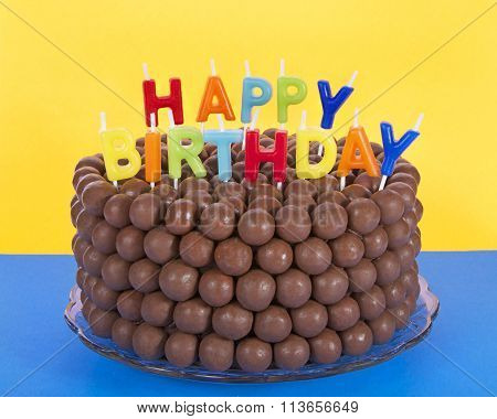 Chocolate cake decorated with rows of malt balls and happy birthday candles on blue table