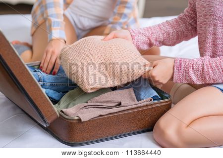 Two sisters are packing baggage.