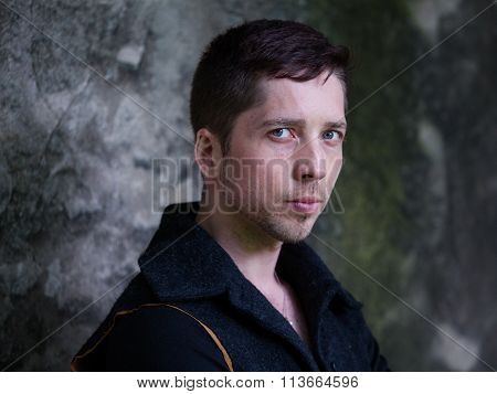 Portrait Of A Handsome Guy On The Background Of Gray-green Concrete Wall