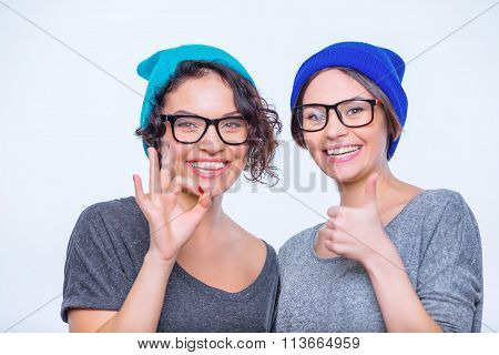 Two young cheerful sisters are posing together.