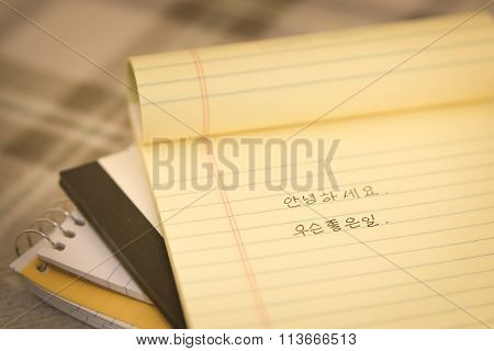 Korean; Learning New Language Writing Greetings On The Notebook