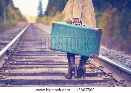 Elegant woman with a suitcase traveling by rail.