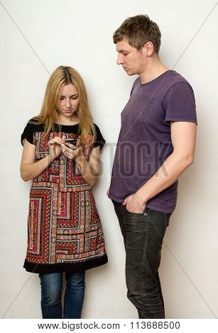 Young Couple Against The Wall, Woman Is Looking At The Screen Of Her Cellphone