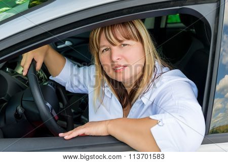 Portrait Of A Mature Pretty Woman Behind The Wheel Of Her Car