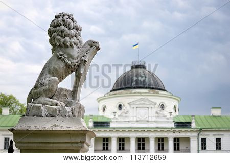 Statue of lion holding a shield in its paws. Regal lion leaning on empty heraldic shield near the castle entrance. The palace and park complex Manor Tarnowski s.Kachanovka Ukraine