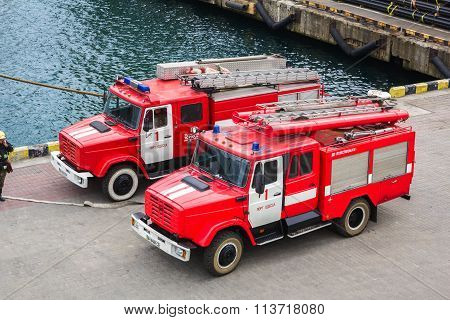 Odesa, UKRAINE - MARCH, 26, 2015: Two firetrucks standing in the sea port on pier during visit of Fr
