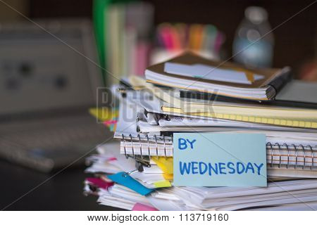 By Wednesday; Stack Of Documents And Laptop At Working Desk.
